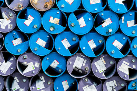 Old chemical barrels. Blue and purple oil drum. Steel oil tank. Toxic waste warehouse. Hazard chemical barrel with warning label. Industrial waste in metal drum. Hazard waste storage in factory. Reklamní fotografie - 137147132
