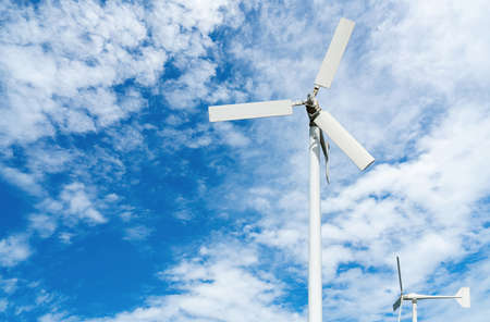 Wind turbine at wind farm on blue sky. Alternative and renewable energy concept. Sustainable electricity. Green energy concept. Small turbine. Clean energy industry. Eco friendly energy. Nature power.