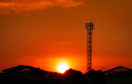 Telecommunication tower with red sunset sky and clouds. Radio and satellite pole. Communication technology. Telecommunication industry. Mobile or telecom 4g network. Silhouette rural house and forest.