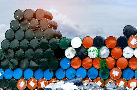 Old chemical barrels. Blue, orange, and black oil drum. Steel oil tank. Toxic waste warehouse. Hazard chemical barrel. Industrial waste in metal drum. Hazard waste storage in factory. Stack of barrel.