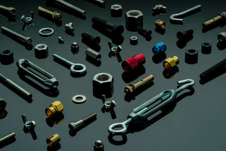 Metal bolts, nuts, and washers. Fasteners equipment. Hardware tools. Different types of nuts, bolts, and screws on table in workshop. Mechanic tools. Threaded fastener use in automotive engineering.