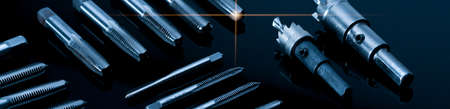 Closeup straight flute tap tip and hole saw on dark background. Industrial tapping tools. Carbide tip metal cutter. Metalworking hardware. Mechanic tools. Drilling equipment. Mechanical engineering.