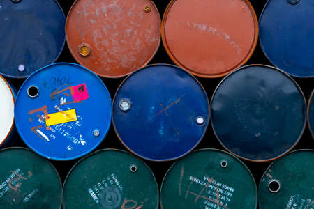 Old chemical barrels. Blue, green, orange oil drum. Steel oil tank. Toxic waste warehouse. Hazard chemical barrel with warning label. Industrial waste in metal drum. Hazard waste storage in factory. Reklamní fotografie