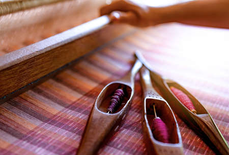 Woman working on weaving machine for weave handmade fabric. Textile weaving. Weaving using traditional hand weaving loom on cotton strands. Textile or cloth production in Thailand. Asian culture. Banque d'images