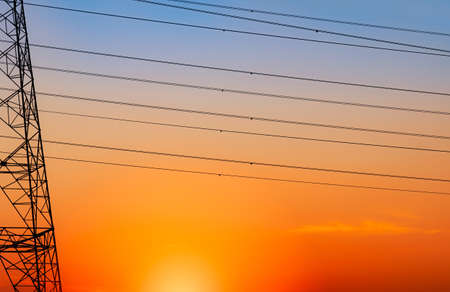 Silhouette high voltage electric pylon and electrical wire with an orange sky. Electricity poles at sunset. Power and energy concept. High voltage grid tower with wire cable at distribution station.  Banco de Imagens