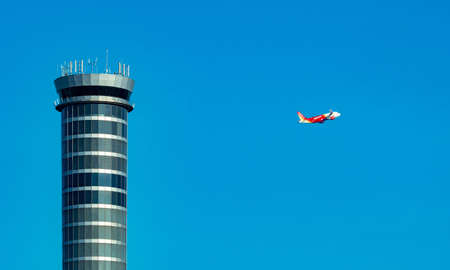 Air traffic control tower in the airport with international flight plane flying on clear blue sky. Airport traffic control tower for control airspace by radar. Aviation technology. Flight management. Foto de archivo