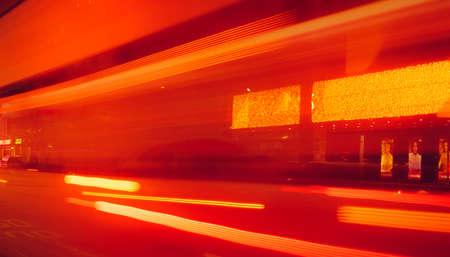 ぼやけた高速車の光と夜の街の通り。建物の横のロッドに赤と黄色の光。夜光の抽象的な背景。道路上の光のぼやけた動き。