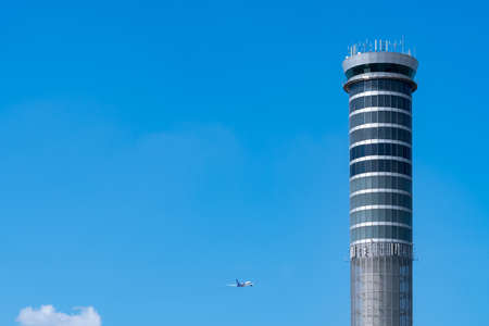 Air traffic control tower in the airport with international flight plane flying on clear blue sky. Airport traffic control tower for control airspace by radar. Aviation technology. Flight management. Standard-Bild