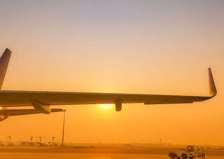 Closeup airplane wing with golden sunrise sky. Plane parked at airfield of airport. Morning flight. Summer travel concept. Pushback tractor support with airport staff at taxiways. Aviation business. Stock Photo