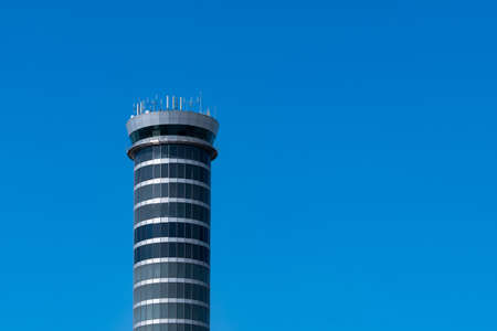 Air traffic control tower in the airport against clear blue sky. Airport traffic control tower for control airspace by radar. Aviation technology. Flight management concept. Modern glass architecture.