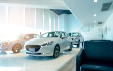 Blurred front view of white car and customer. New luxury car parked in modern showroom. Car dealership office. Electric car business concept. Automobile leasing. Showroom interior building design.