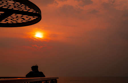 Backpacker watching sunset over the sea at Laem Thaen viewpoint, Chonburi, Thailand. Beautiful orange sunset sky. Back view of a man travel alone. Summer travel at tropical sea. Chillout at seaside. Stock Photo