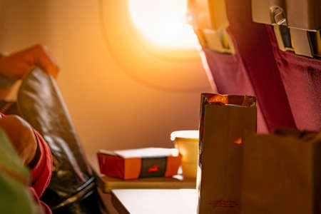 Food in brown paper bag put on plastic airplane tray table at seat back with blurred passenger hand opened black leather bag. Sunlight passing through the economy class airplane window into the plane.