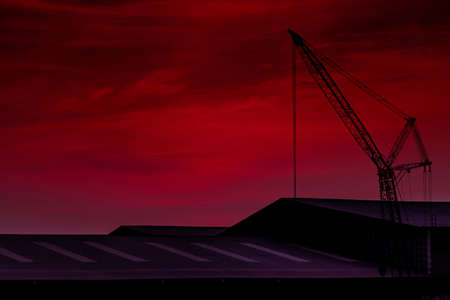 Construction crane against pink sky and clouds. Roof of building. Crane use reel lift up equipment in construction site. Crane for rent. Crane dealership for construction business. Romantic sky. Standard-Bild