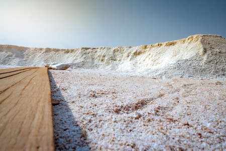 Low angle view of brine salt farm with blue sky. Pile of organic sea salt near warehouse. Raw material of salt industrial. Ocean salt. Sodium chloride mineral. Summer travel in Thailand concept.
