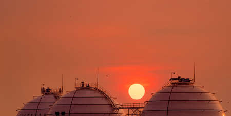 Industrial gas storage tank on orange sunset sky. LNG or liquefied natural gas storage tank. Spherical gas tank in petroleum refinery. Above-ground storage tank. Natural gas storage industry.