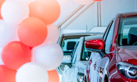 Front view of red SUV car in showroom. New luxury car parked in modern showroom for sale. Car dealership office. Automobile retail shop. Electric car technology and business. Automobile rental.