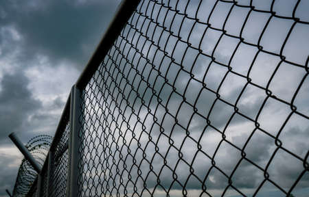 Military zone mesh fence. Prison security fence. Looking up view of barbed wire security fence with storm sky and dark clouds. Razor wire jail fence. Barrier border. Boundary security wall. Banque d'images