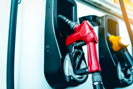 Petrol pump filling fuel nozzle in gas station. Stock Photo
