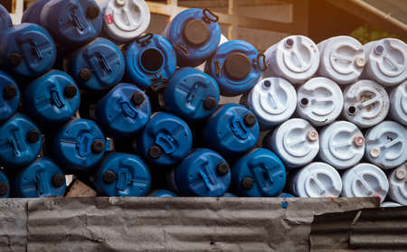 Selective focus on empty old chemical barrels. Blue and white oil drum. Plastic oil tank. Toxic waste warehouse. Hazard chemical barrel. Industrial waste plastic drum. Empty can and QC pass label.
