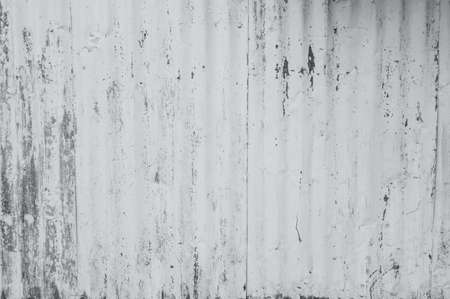Galvanized sheet painted with white color. Empty white wall texture background. Peeling paint on white wall. Distorted striped gray galvanized sheet. Empty white and gray background for minimal life. Archivio Fotografico