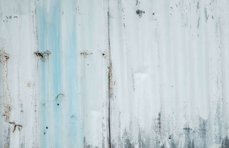 Galvanized sheet painted with white color. Empty white wall texture background. Peeling paint on white wall. Distorted striped gray galvanized sheet. Empty white and blue background for minimal life.