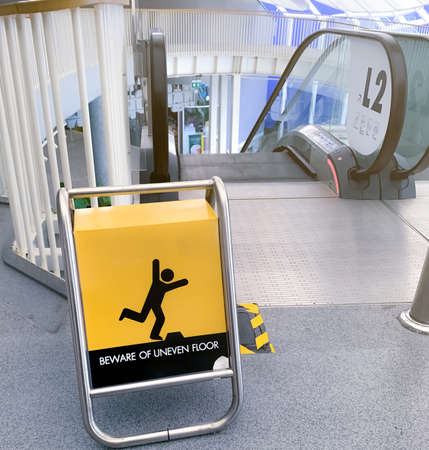 Beware uneven floor warning sign on yellow board in front of escalator in shopping mall. Beware uneven floor warning sign for safety at walkway before dawn way of escalator. Notice for safety. Banque d'images