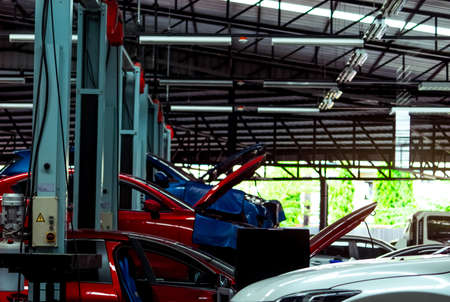 Auto repair shop. SUV car is lift in garage for repair and maintenance service. Auto service with lifted vehicle. Car body lifted in workshop for inspection. Car check up at service station.
