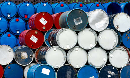 Stack of old chemical barrels. Blue, black and red oil drum. Steel and plastic oil tank. Toxic waste warehouse. Hazard chemical barrel. Industrial waste in drum. Hazard waste storage in factory.