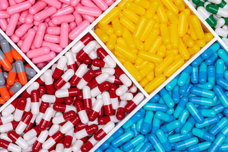 Top view of colorful capsule pills in plastic tray. Pharmaceutical industry. Healthcare and medicine. Drug production. Pharmaceutics concept. Vitamins and supplements capsules. Bright color capsule. Stok Fotoğraf