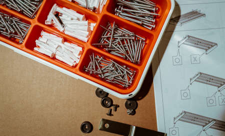 Screws and wall plug in orange plastic box. Top view tool box on brown background with dish drying rack assembly instruction. Set of screws and plastic plug for drilling wall and installation things.