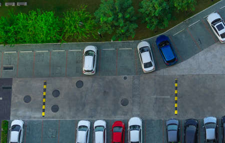 Above view of cars parked at car parking area of the apartment. Aerial view concrete car parking lot with speed bump near green trees in the park. Outdoor car parking space with empty slots.