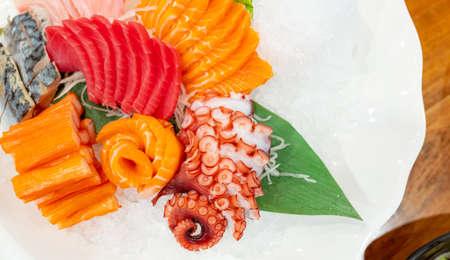 Japanese food combo set. Salmon, tuna sashimi, giant octopus and Crab sticks serve with crushed ice in white plate on restaurant table. Fish meat sliced. Seafood buffet. Healthy Japanese food.