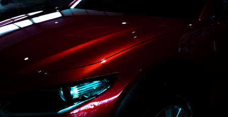 Selective focus on shiny red luxury SUV car in showroom. Elegant electric car with sport design. Car parked in showroom. Car dealership. Electric vehicle development concept. Future transportation.
