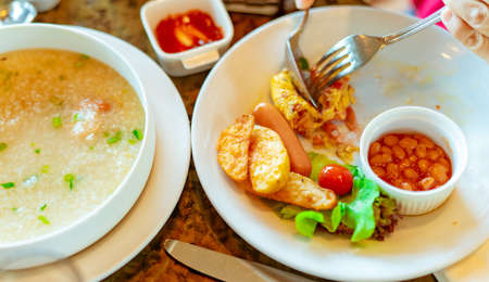 Person use fork and spoon eating breakfast at restaurant. Rice porridge or rice gruel with shrimp in white bowl and sausage and potatoes slices fried. Breakfast meal for healthy life. Healthy food.