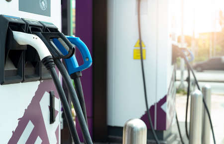 Electric car charging station for charge EV battery. Plug for vehicle with electric engine. EV charger. Clean energy. Charging point at car parking lot. Green power. Future transport technology. Banco de Imagens