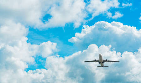 Commercial airline flying on blue sky and white fluffy clouds. Under view of airplane flying. Passenger plane after take off or going to landing flight. Vacation travel abroad. Air transportation. Stock fotó