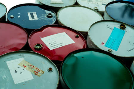 Old chemical barrels. Blue, green, and red oil drum. Steel oil tank. Toxic waste warehouse. Hazard chemical barrel with warning label. Industrial waste in drum. Hazard waste storage in factory. Stock fotó