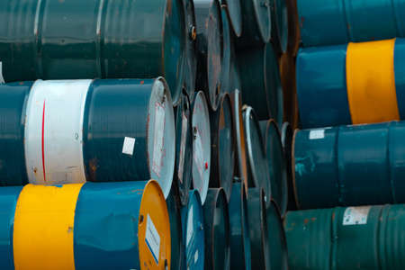 Old chemical barrels stack. Blue, green, and yellow chemical drum. Steel tank of flammable liquid. Hazard chemical barrel. Industrial waste. Empty chemical barrels at the factory warehouse. Banco de Imagens