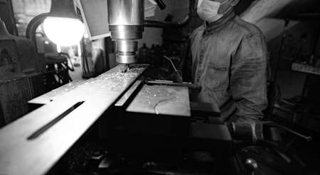 Milling machine working near worker with a protective mask. Tool for cut metal workpiece. Vertical milling machine with cemented carbide milling cutter. Steel manufacturing industry. Milling process. Stock fotó