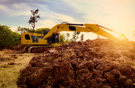 Backhoe working by digging soil at construction site. Excavator digging on earth. Earthmoving machine. Backhoe for rental business background. Pile of brown soil after digging by yellow excavator. Stock fotó