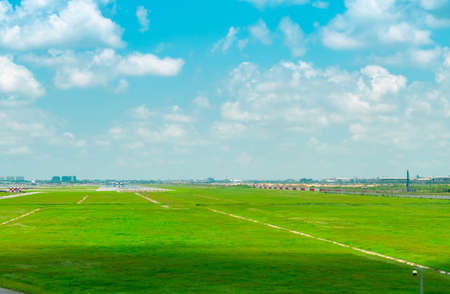 Landscape of the airport runway and green grass field with blue sky and white clouds. Plane on taxiway. Airplane take off at taxiway of the airport. Aviation business. Cityscape aroud the airport.