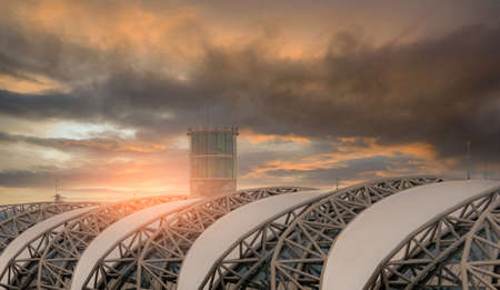 Selective focus on airport roof and blur air traffic control tower in the airport against dark cloudy sky. Steel structure of airport roof. Exterior building architecture with geometric modern design.