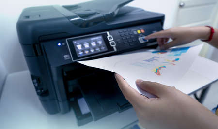 Office worker prints paper on multifunction laser printer. Copy, print, scan, and fax machine in office. Document and paper work. Print technology. Hand press on photocopy machine and holding paper.