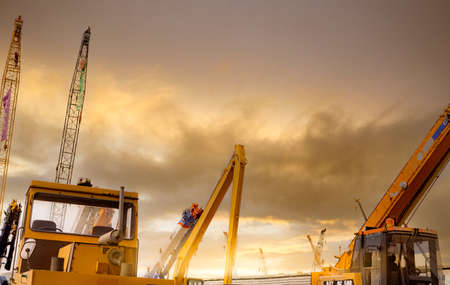 Yellow bulldozer, backhoe, and crawler crane parked at second-hand machinery auction yard with sunset sky and sunlight. Heavy machinery for rent and sale. Crane dealership for a construction business.
