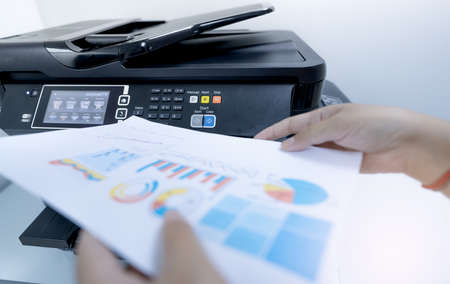 Office worker prints paper on multifunction laser printer. Copy, print, scan, and fax machine in office. Document and paper work. Print technology. Blurred hand hold printed paper. Scanner equipment.