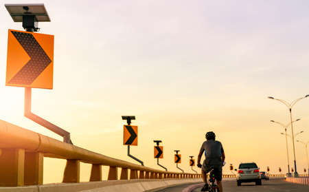 Back view of man wears helmet riding bicycle on the curve road behind cars. Safety driving and riding on the road. Curve road traffic sign with solar panel energy. Outdoor exercise. Healthy lifestyle. Stock fotó