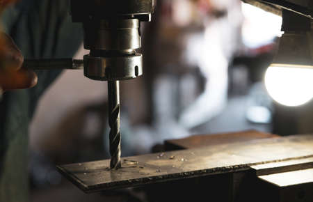 Worker hand working on milling machine to change metal drill bit. Tool for drilling metal workpiece. Milling machine. Steel manufacturing industry. Metal work industry. Industrial drilling machine. Stock fotó