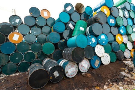 CHACHOENGSAO, THAILAND-JUNE 24, 2021 : Old chemical barrels stacked. Steel tank of plasticizer with label. Blue, green, black, and yellow chemicals barrels. Industrial drum. Hazard waste in factory.
