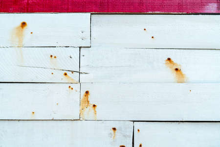 White wooden wall texture background. Wood plank surface texture background. Timber wooden wall texture background. Exterior design. The orange color of rusty nails stains on a white wooden wall.